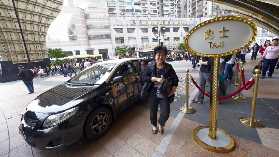 Macau, Macau S.A.R. - April 3, 2011: a chinese woman step out from a taxi at the entrance of Grand Lisboa, an hotel and Casino complex.