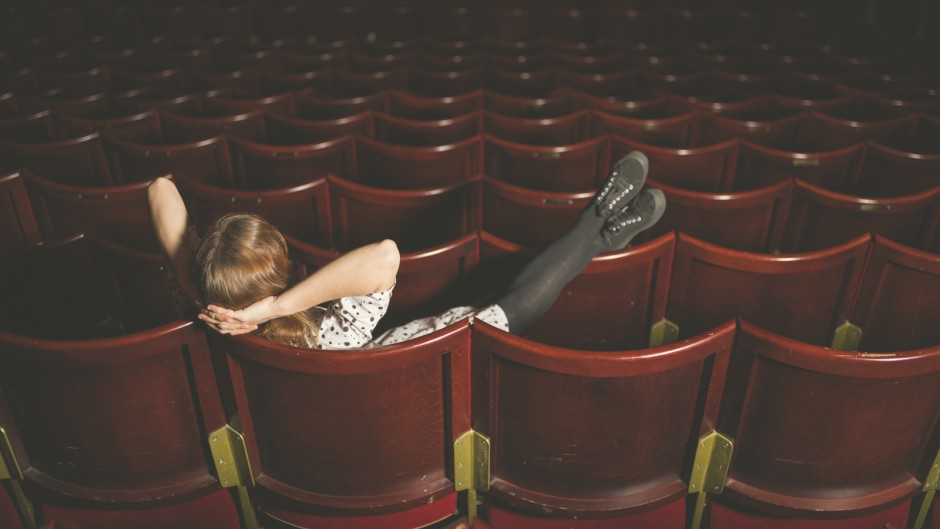 A young woman is sitting in an auditorium with her feet on the seats in front