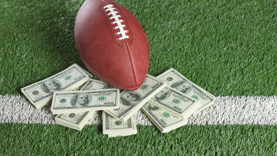 An NFL football sits with a pile of money on a green field