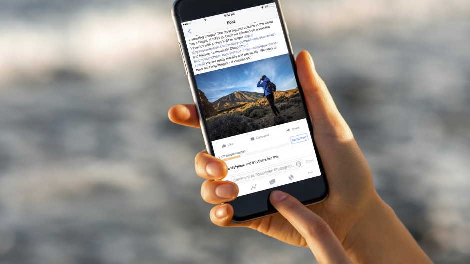Gran Canaria, Spain - December 13, 2015: Woman watching Facebook news from RossHelen account with new iPhone 6s Space Gray on the blurred sea background. iPhone 6 was created and developed by the Apple inc. Facebook is an online social networking service founded in February 2004 by Mark Zuckerberg with his college roommates. RossHelen is famous travel stock photographers.