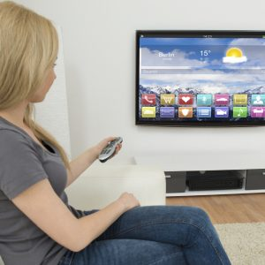 Young Woman On Sofa Holding Remote Control In Front Of Television With Apps