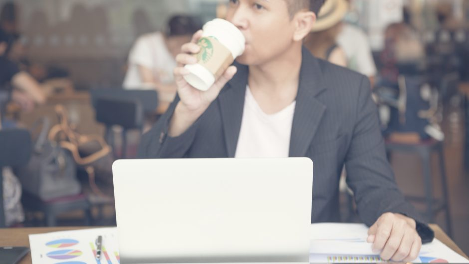 Bangkok, Thailand - September 6, 2015: Business man to drinking a tall Starbucks coffee in front of working on a laptop computer.