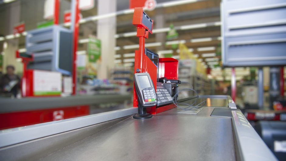 Empty cash desk with payment terminal and customers in queue in supermarket