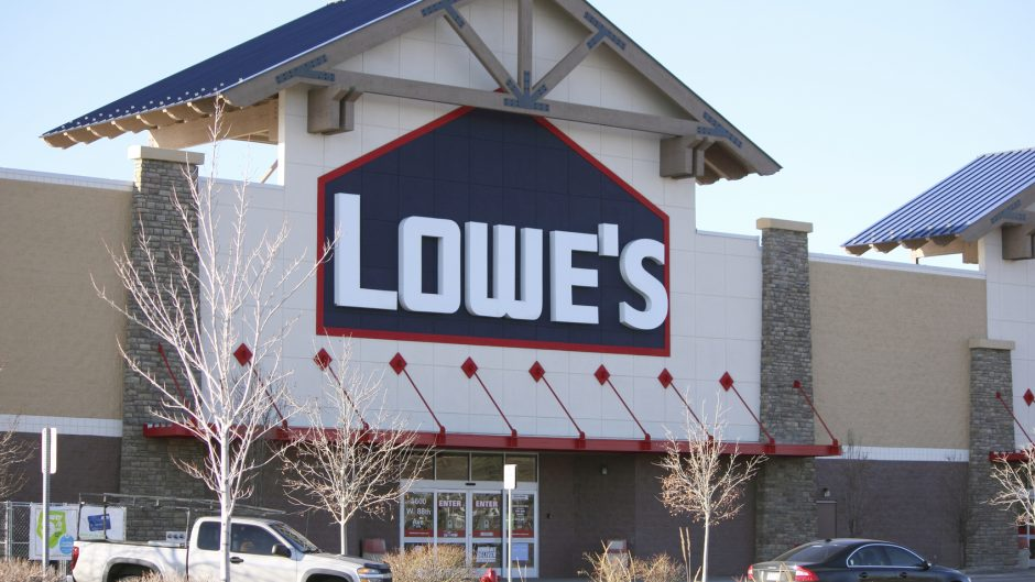 """Westminster, U.S.A.  -  March 9, 2012:  From the parking lot of a Lowe's retail store.  The large Lowe's sign is in white, dark blue and red, above the entrance doors.  Customer vehicles are in the parking lot."""