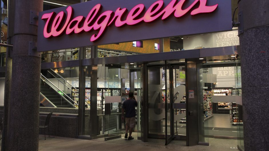 Boston, United States - June 9, 2013: Shopper enters Walgreens store on June 9, 2013 in Boston. Walgreens is the largest drug retail chain in the United States with 8,300 stores in 50 states.